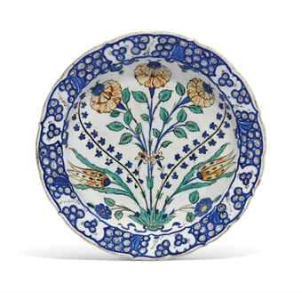 AN IZNIK POTTERY DISH - OTTOMAN TURKEY, CIRCA 1565 - With cusped sloping rim on short foot, the reverse with alternating paired tulips and flowerheads, both in cobalt blue and black, foot and rim drilled, hair crack, otherwise intact 11¾in. (29.8cm.) diam.
