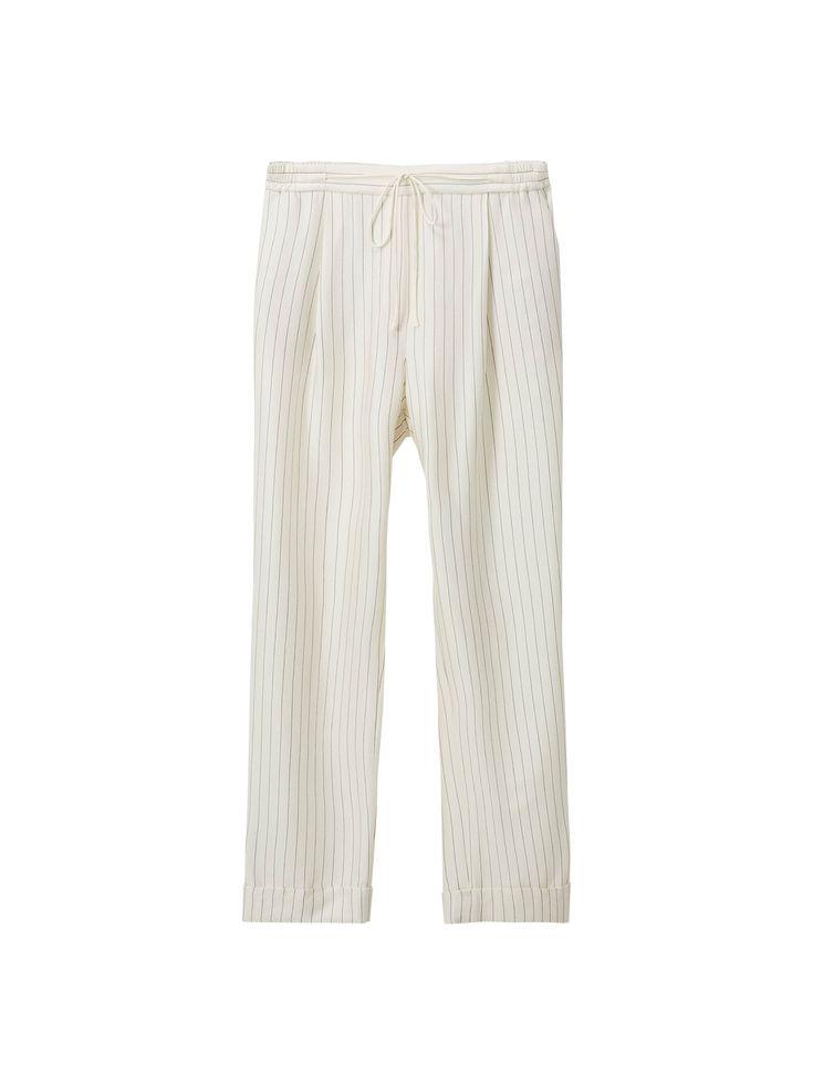 Pantalon à rayures tennis et patte décorative. Coupe jogging, taille élastique avec lien ajustable, deux poches sur les côtés, deux poches passepoilées à l'arrière et revers dans le bas.