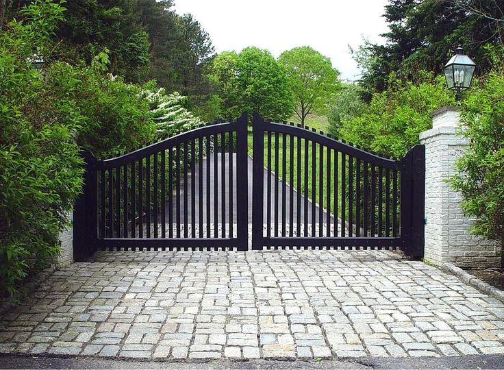A transitional-style driveway gate features the arch and pickets of a traditional entry gate, but with a black finish and contrasting white brick pillars that update the look. Gate designed and installed by Tri State Gate in Bedford Hills, New York.
