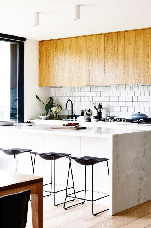 Wood upper kitchen cabinets in this bright kitchen with white island and black stools.