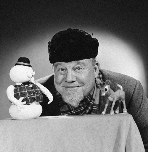 """December 1964: Folk singer Burl Ives poses with Sam The Snowman and Rudolph from """"Rudolph The Red-Nosed Reindeer"""", a Christmas television special produced in stop motion animation by Rankin/Bass which ran on NBC from 1964-1972 and CBS from 1972-Present Day.  Ives provided the voice of Sam, the narrator, as well as contributed songs to the show.  Photo: NBCU/Photo Bank"""