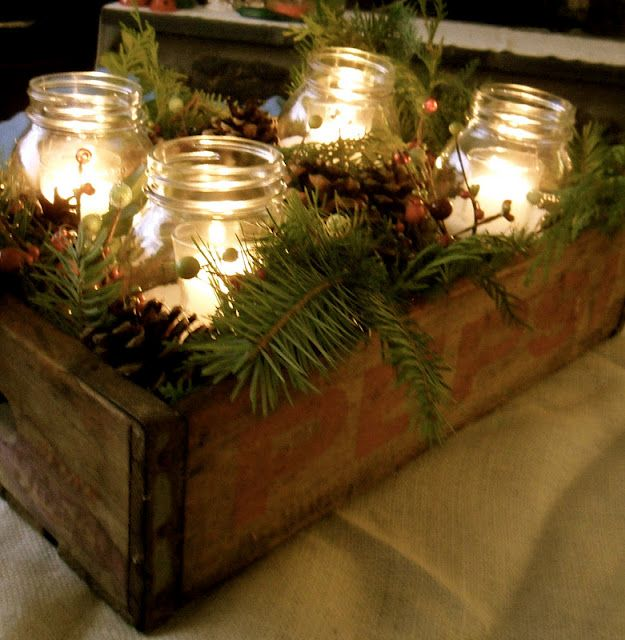 Winter rustic crate and pine centerpiece filled with candlelit Mason jars.
