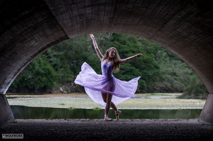 A beautiful young dancer with long hair dancing in a river causeway wearing a lilac outfit