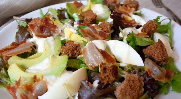 Kook de eieren in 6-7 minuten hard. Laat schrikken, pel ze, en houd apart.     Bak het ontbijtspek uit in een droge koekenpan, tot de reepjes knapperig zijn. Laat even uitlekken op een keukenpapiertje en houd apart.     Verdeel de romaine sla over twee borden. Verdeel de avocado en de lenteui erover.      Pel de eieren, snijd ze in partjes, verdeel over de salade.      Breek het ontbijtspek in stukjes en verdeel over de salade, en doe hetzelfde met het beschuitje - dat is mijn makkelijke…