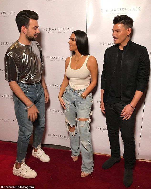 She's back with a vengeance: Kim Kardashian glowed - literally - at her makeup Masterclass in Dubai on Friday (pictured with fan and makeup artist Serhat Şen on left and her makeup artist and Masterclass creator Mario Dedivanovic on the right)