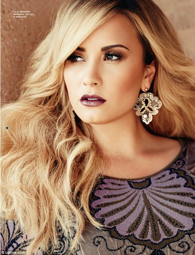 Stunning: In another shot, the star strikes a sultry pose wearing mauve lipstick and sparkling earrings - Demi Lovato