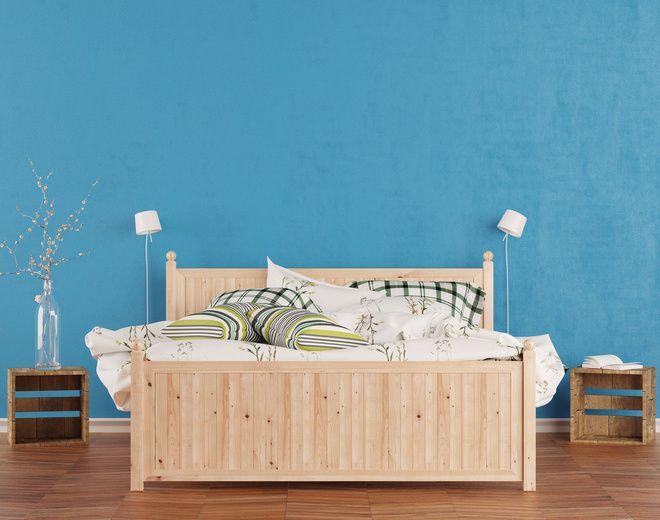 Belle couette en duvet d'oie sur lit en bois dans un décor très minimaliste.