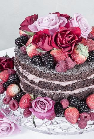 Naked chocolate cake with flowers and fruit