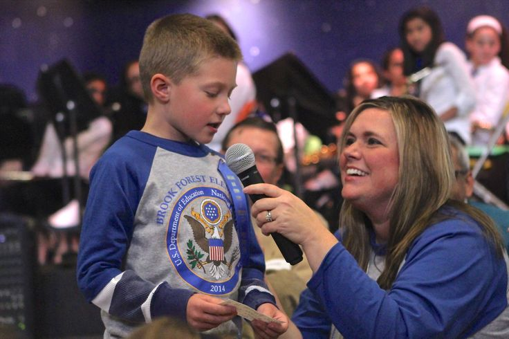 Principal Kelly Voliva listens as student Zach Koutsky talks about why he loves Brook Forest during a ceremony to celebrate the elementary school's National Blue Ribbon Award.