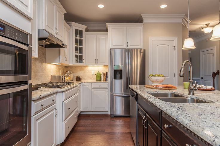Dark cabinets in the island contrast with main cabinets in gleaming white. New homes in the Steele Creek community built by Eastwood Homes in Charlotte, NC.