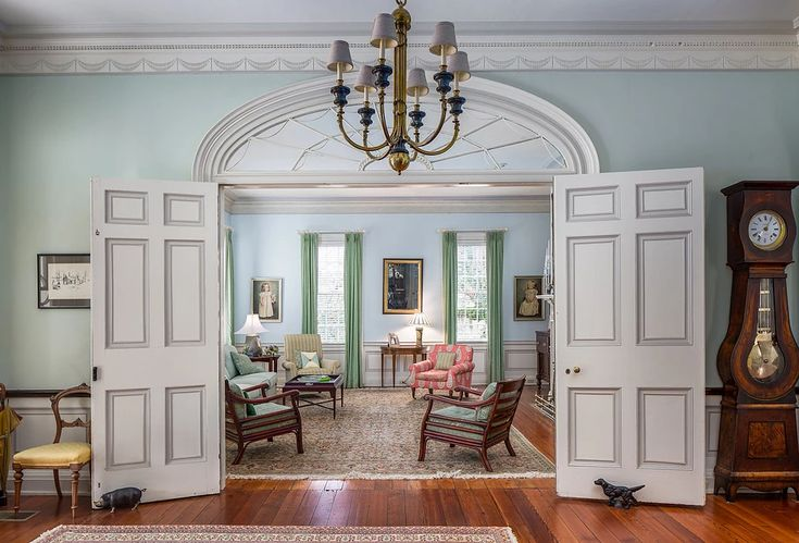 Interior Designer | Seabrook | J. Jilich Design & Associates  Plantation style living room, with a large chandelier, and blue walls.  Antique grandfather clock, and chairs.  Traditional window treatments, rugs and fabrics.  Historic Renovation