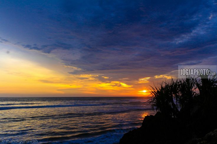 Pemandangan indah matahari terbenam di kaki tebing pantai parangtritis yogyakarta.