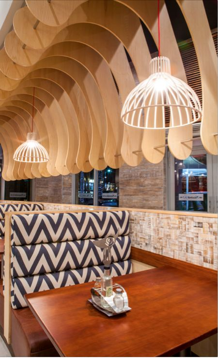 This just says Hlala Phansi! Beautiful wooden fins suspended over the seating areas create a bold statement furthered by the Jacque Cronje fin pendant lights and Chevron fabric from Hertex - Nando's Gateway