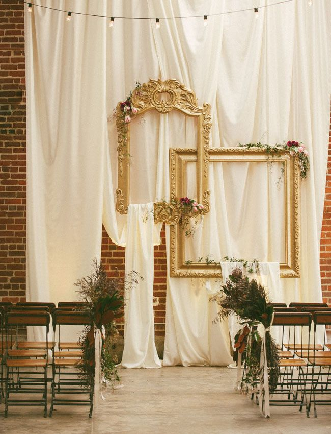Hang empty gold frames + draped fabric for an easy and romantic idea for wedding decor/ a ceremony backdrop