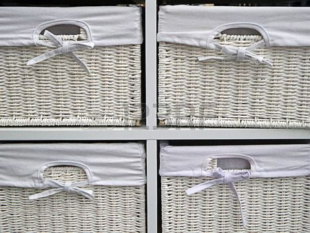 White boxes from braided bamboo with canvas cover used for storage objects in the house.