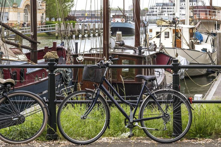Rainy spring day in the harbor of Rotterdam with bicycles and vintage boats.