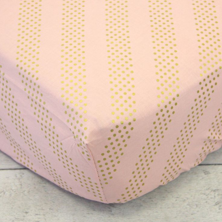 This is a gorgeous blush color fitted crib sheet with adorable gold polka dot stripes on the diagonal.
