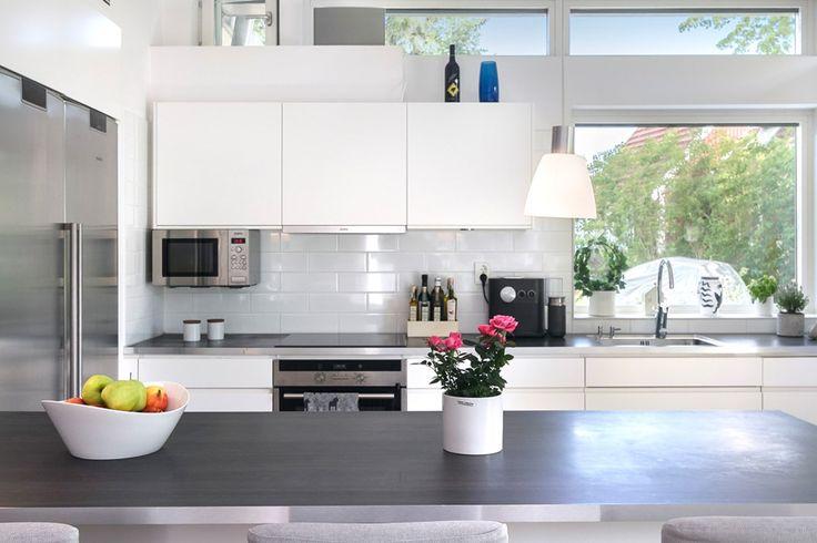 Modernt kök från Ballingslöv med gott om förvaring och alla tänkbara faciliteter. Vita skåp samt mörk arbetsbänk med vitt kakel över. Köksö med förvaring under samt bardel mot vardagsrummet.