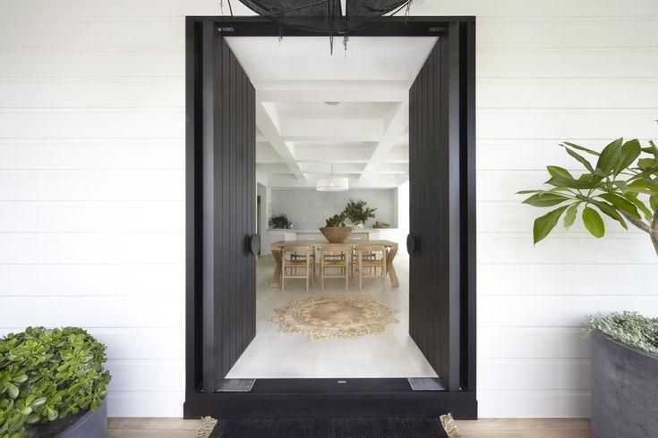 White weatherboard cladding, black double doors, plants in grey pots