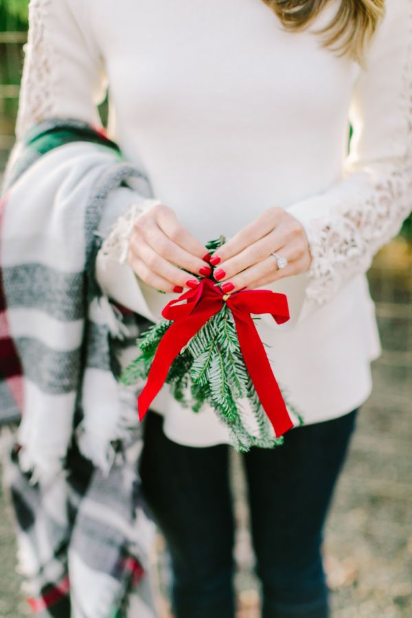 Hearts are light, the season is bright and you're getting married! For a chic and stylish holiday-themed announcement, all you need are poppy red nails, a cozy plaid blanket and a festive bunch of mistletoe to show off your new engagement ring in some engagement photos. | 10 Wonderful Winter Engagement Announcement Ideas