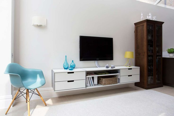 Lots of storage that floats above the floor and beneath the TV. Result: the room feels bigger