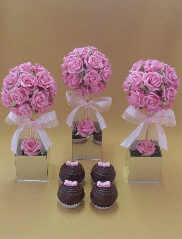 Topiaria de rosas em e.v.a. na cor rosa, em vaso de vidro espelhado com laço fita de cetim. O acabamento é feito com musgo desidratado. O arranjo todo mede aproximadamente 33 cm de altura e a topiaria tem 14 cm de diâmetro. O vaso mede 8,5 cm de altura x 8,5 cm de largura. R$ 59,90