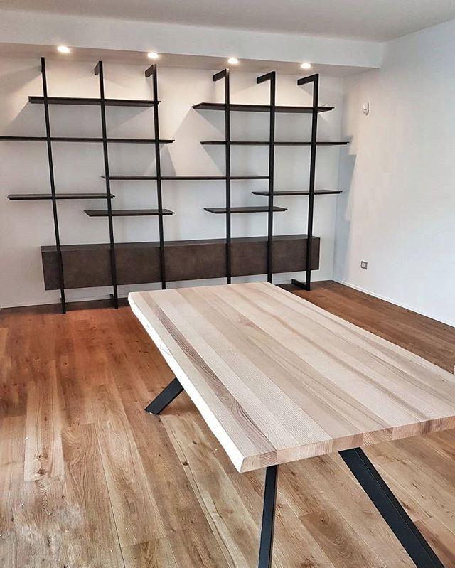 Soggiorno con parete attrezzata composta da mensole e mobili ...