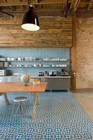 Cozinha aberta, com ladrilho hidráulico no chão e metade da parede. Tijolo a mostra no resto da casa.