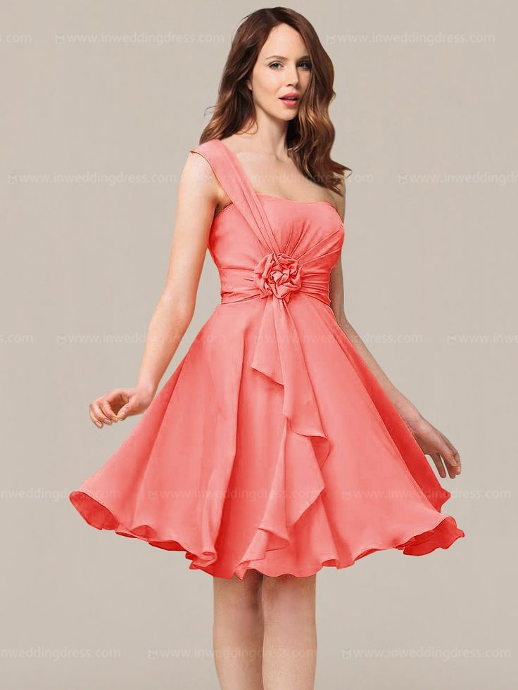 Casual bridesmaid gown features in chiffon. The one-shoulder strap overlays the bodice to the waist both front and back with a tapered look.  The bodice is gathered off center to meet a rosette on the waist. A cascading ruffle accents the short length skirt. Zipper back. Available in 60 colors, shown in Coral.