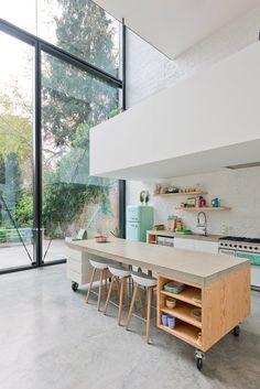 Une cuisine blanche moderne avec du beton ciré au sol.