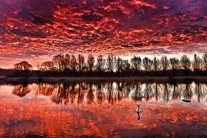 The sky looks on fire as the clouds glow red in a rowing lake in Nene Park in Peterborough, UK