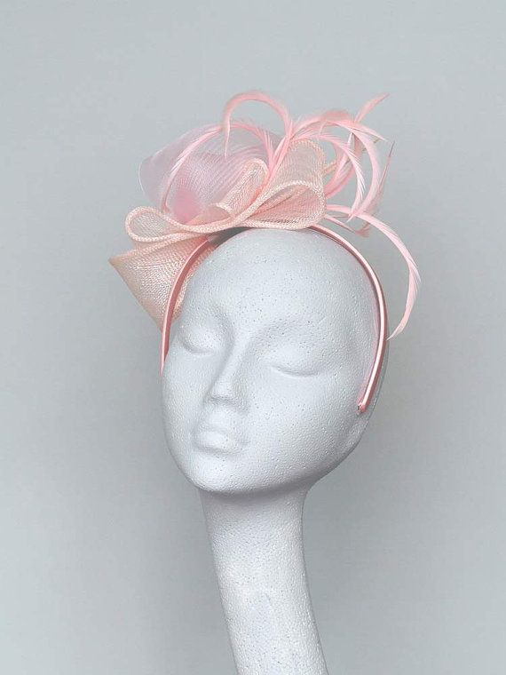 Pale pink sinamay fascinator features a loose bow, crin and feather trimming. Set in a pink satin headband.  A lovely accessory for that special