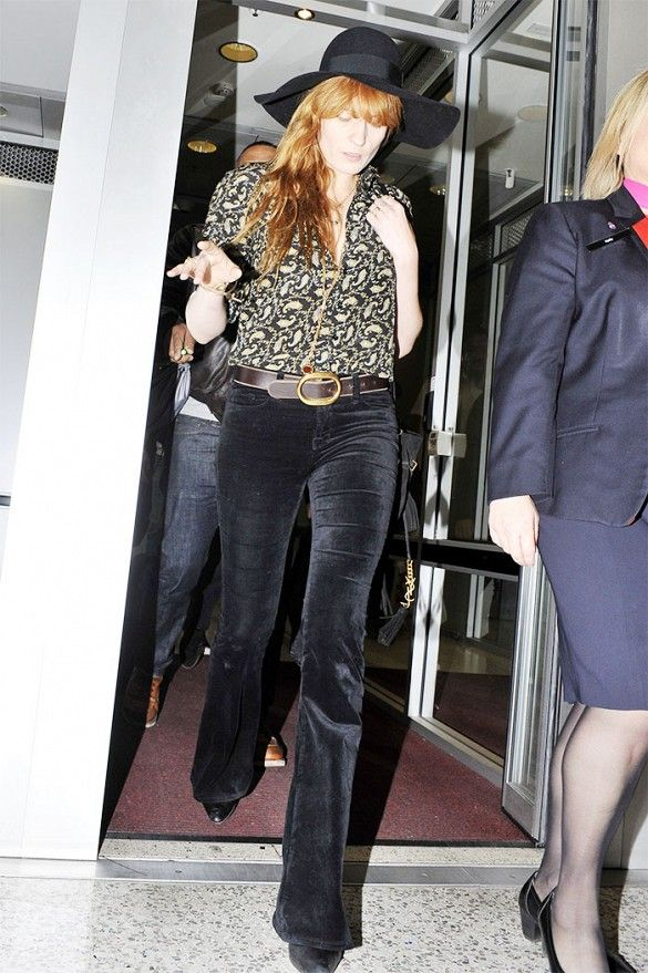 Florence Welch wears a patterned button-up top with velvet flared pants belted at the waist and a black hat.