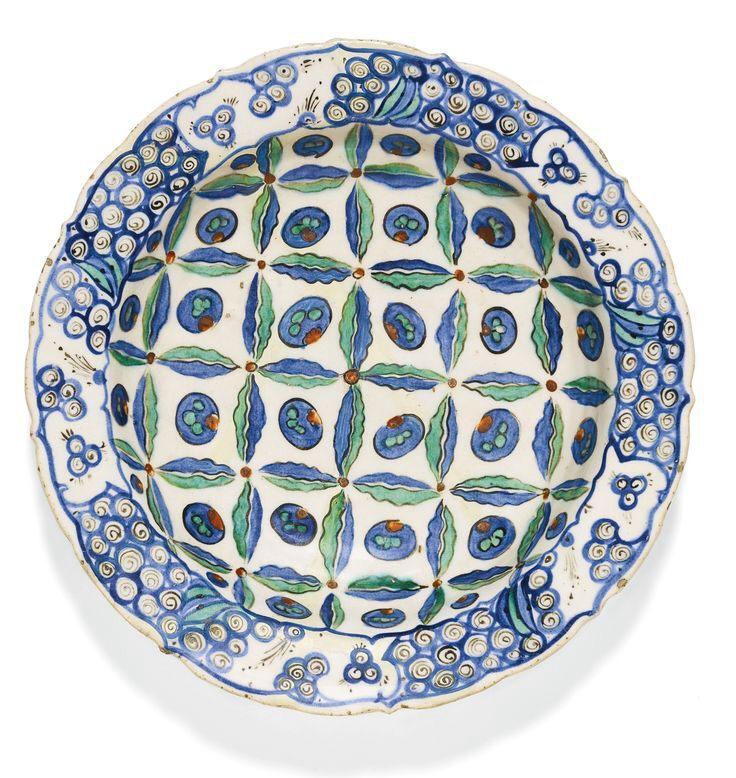 An Iznik polychrome pottery dish with stylised cloud and cintamani design, Turkey, circa 1580-85, of deep round form with a slightly bracketed everted rim, decorated in underglaze cobalt blue, viridian green, relief red and black outlines with an abstracted cloud and cintamani pattern in the centre and scrolling cloudbands on the rim, foliate motifs on underside, old collection label to underside 31cm. diam.