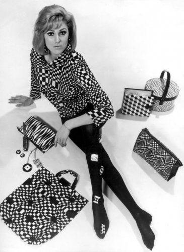 Op-art mode, mode met zwart-witte grafische dessins die optische effecten teweeg brengen. Studio-opname van model met op-art truitje en maillot aan, ze zit op de vloer omringd door op-art tassen, oorbellen, kettingen, hoedendoos, toilettas en een singletjes-map. 1966.