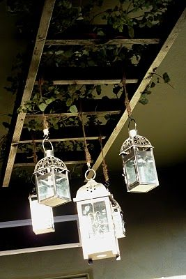 Love this idea, an old ladder attached to ceiling then hang lanterns. Such a cozy patio trick.