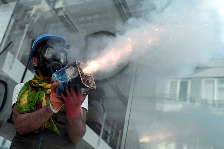 A protester wearing a gas mask holds a box of fireworks during clashes against riot police in Taksim Square, on June 11, 2013