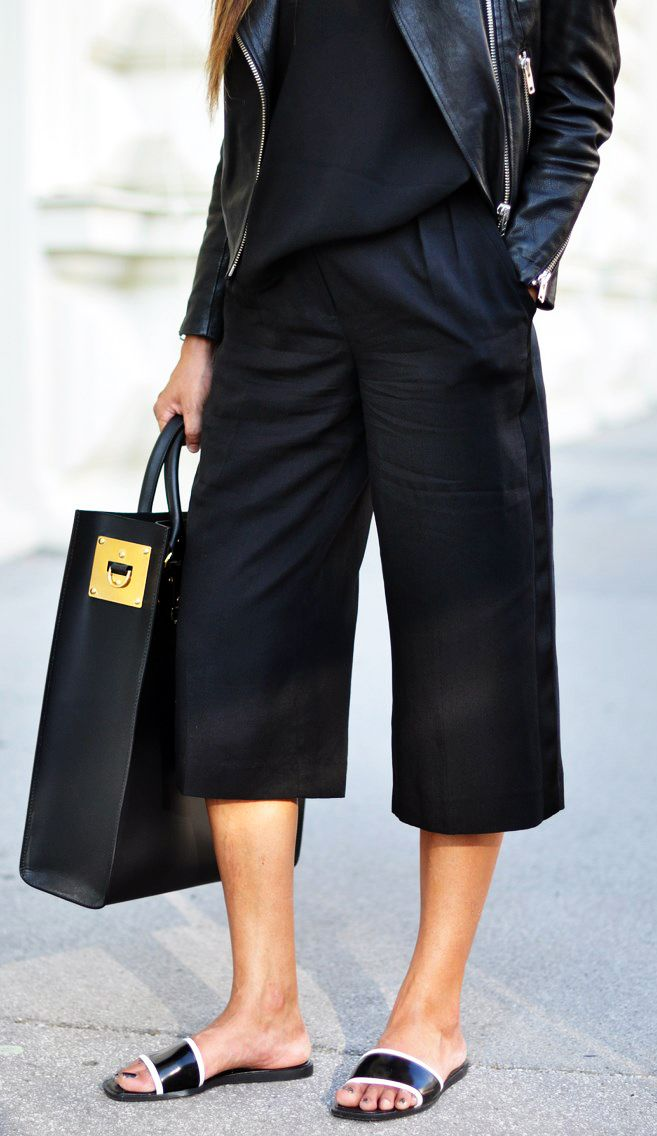 Laura Dittrich is wearing black culotte shorts from Mango, leather jacket and cami from H&M, slides from Zara and the bag is from Sophie Hulme