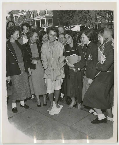 A barefoot student standing on a towel is surrounded by her classmates. (Caption on back: Fire in Mary Foust Dormitory 12/1956 Mary Anges Hippard from New Jersey)