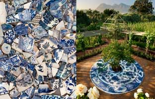 blue & white china tile patio in the center of the garden w/ a small peach tree in the center