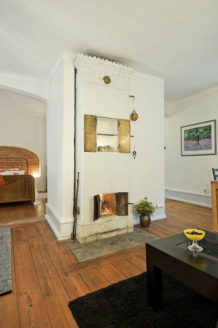 Breda golvtiljor och fungerande kakelugn i vardagsrummet på plan ...