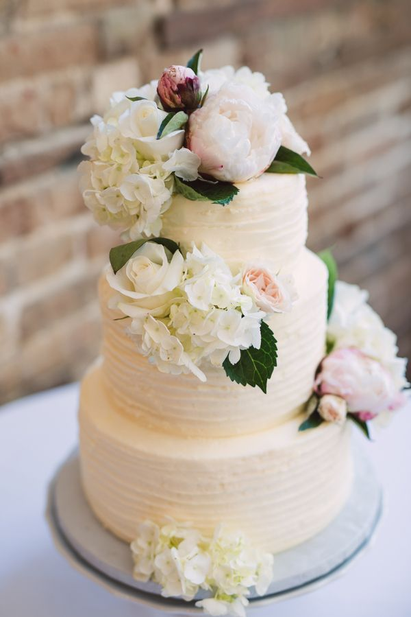 A three-tiered white wedding cake with combed icing and a cascase of fresh flowers, including blush-colored peonies and creamy hydrangeas | Photo by Treebird Photography