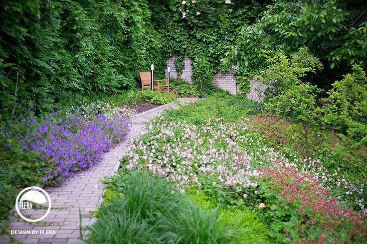 Krasna zelena zahrada s kvetmi, posedenim a chodnikom