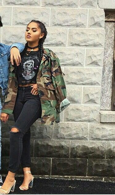 Tough looking. Love the braids with the camo jacket, black graphic shirt & black ripped skinny jeans