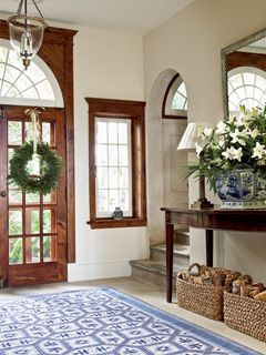 Amazing entryway- of course, I love the rug- ties in so well with the blue & white planter. And the architectural detail? Just great!