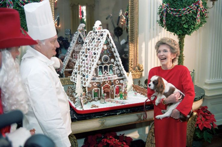 Chef Hans Raffert and First Lady Nancy Reagan enjoy the gingerbread house holiday spirit as Rex, the Reagans' Cavalier King Charles spaniel, looks on in December 1984.