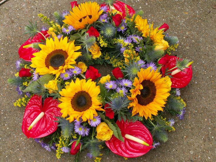 a loose wreath made with sunflowers, bright red anthuriums, september flower and some thistles