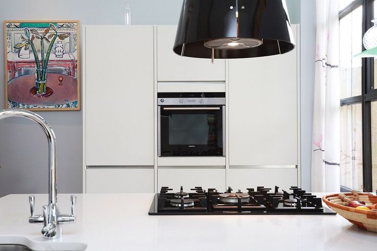 White gloss glass kitchen units in a two tone kitchen design with Salento Beige grey kitchen island.