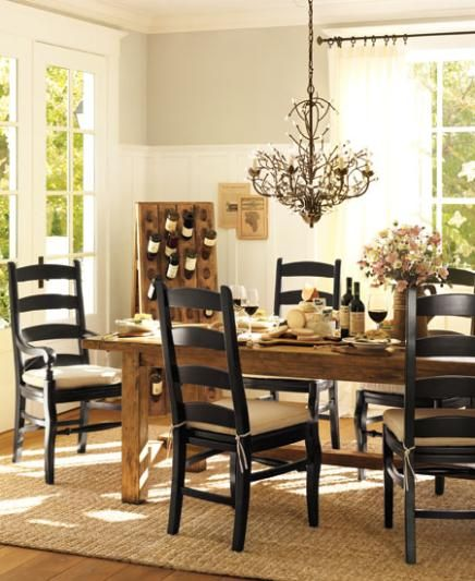 Black chairs with white cushions, natural table, fiber rug, lots of light