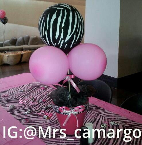 The zebra print center piece i made using wooden dowels clay flower pot styrofoam balls tissue paper ribbon and balloons. Rains first birthday. Zebra centerpiece i got down if i say so myself. Ig follow!!